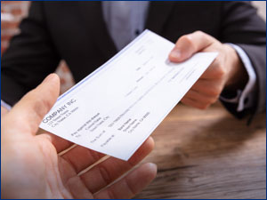 Person handing a check to another person.