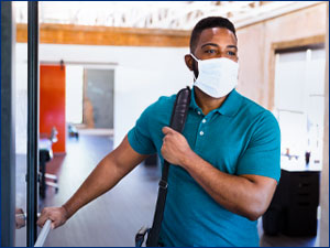 A man wearing face mask walking into a building