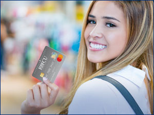 Woman smiling and holding RBFCU credit card