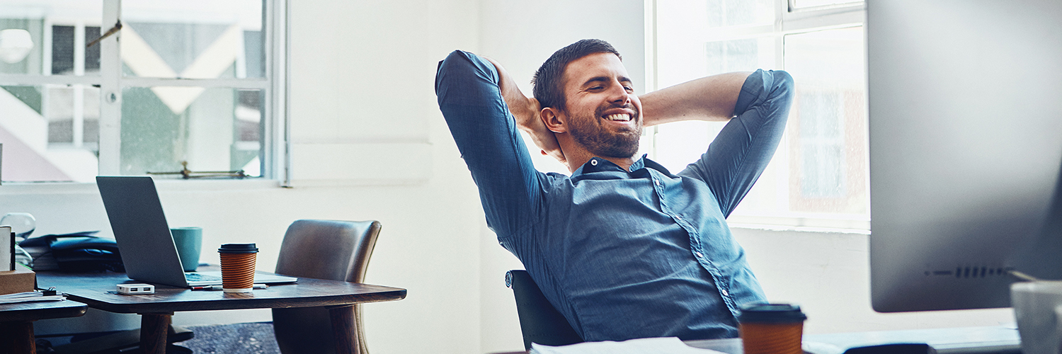 Man leaning back in his chair at his desk at work
