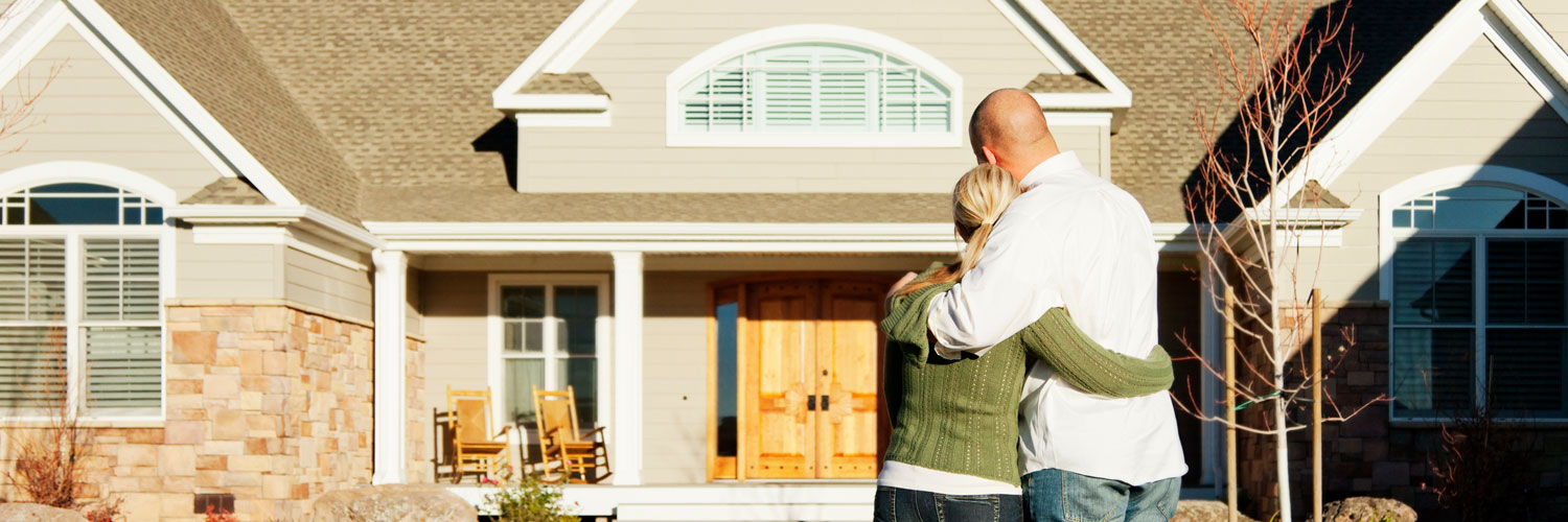 Couple hugging and looking at their home