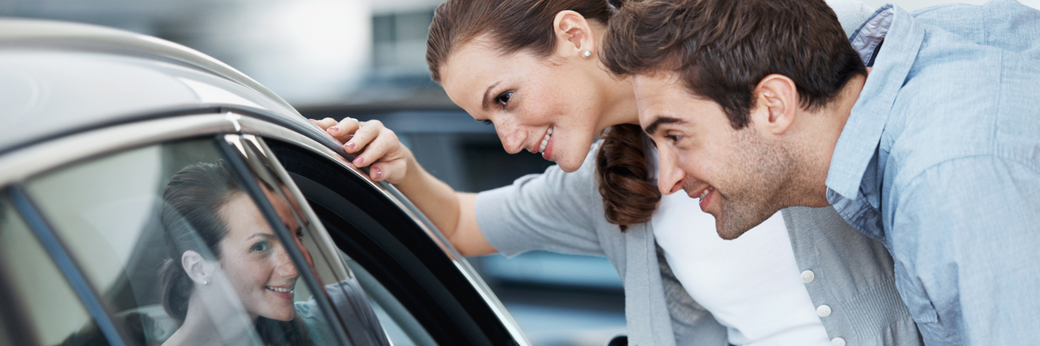 Two people looking at car for sale