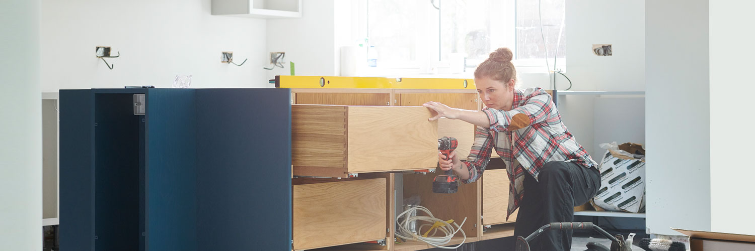 Woman working on cabinets inside a home
