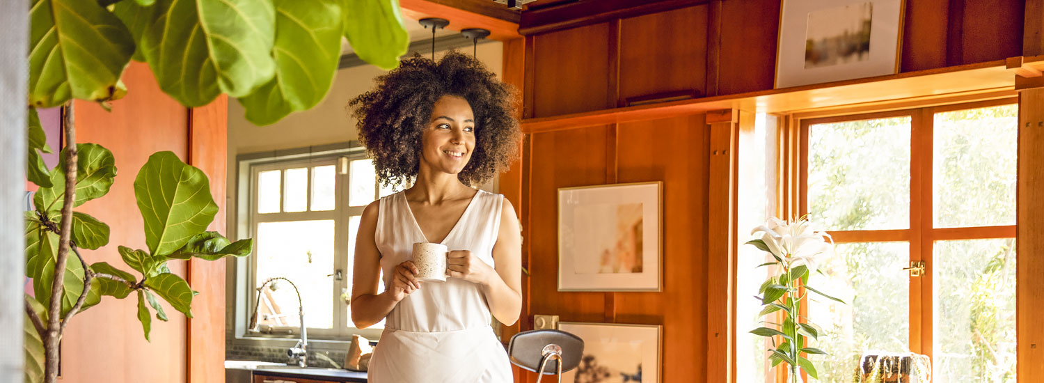 Woman holding coffee cup and standing in her home