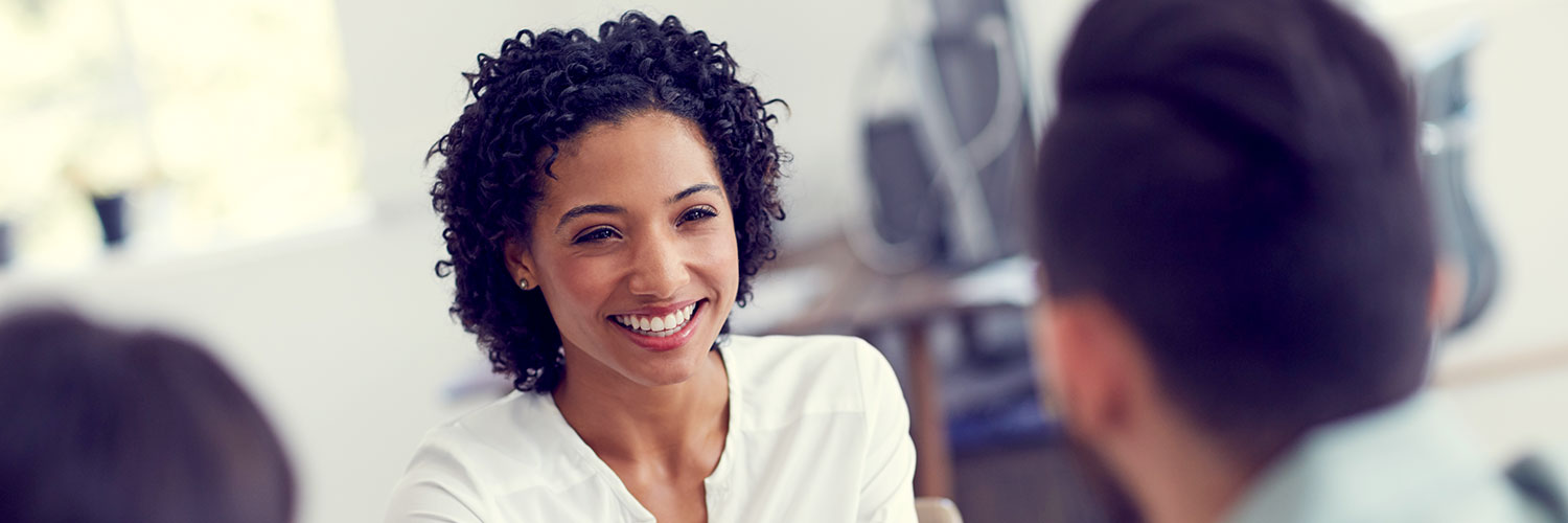 Woman smiling at person sitting across from her