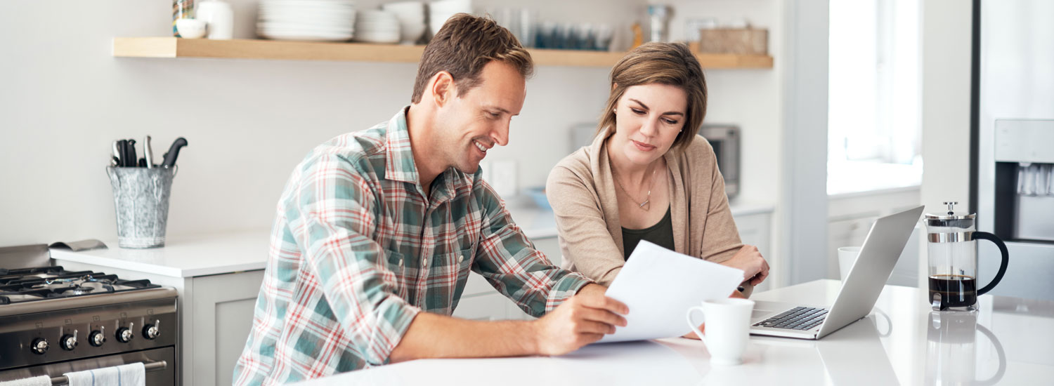A man and woman looking at a paper and laptop