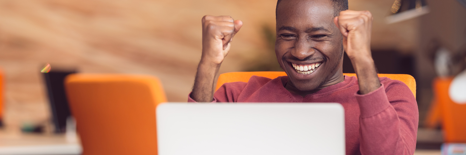 Excited person looking at computer screen