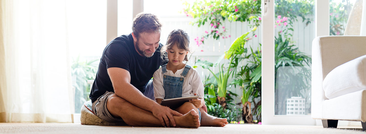 Father and daughter using tablet device.