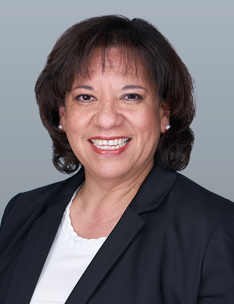 an image of Zulema Martinez wearing a black jacket and a white shirt